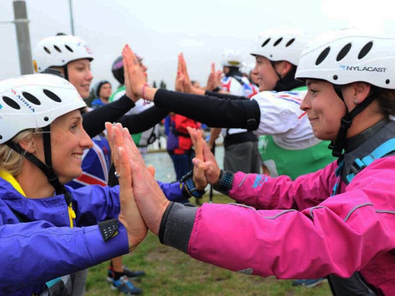 Member FAQs. Female paddlers supporting each other.