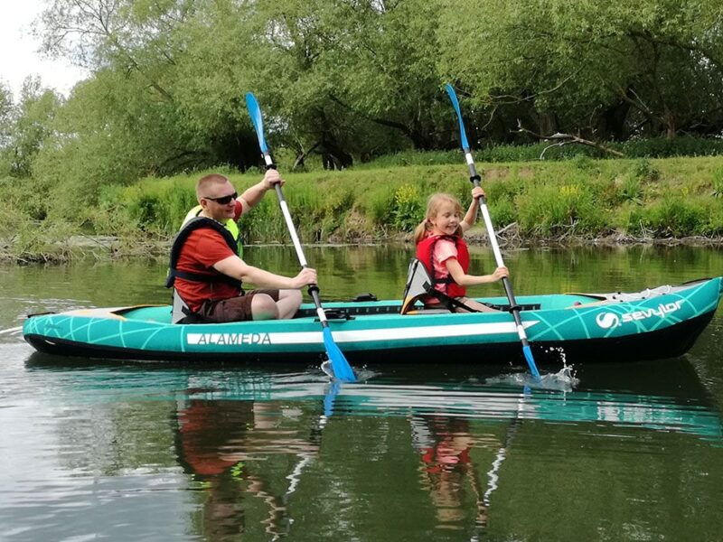 Father and daughter paddling an inflatable kayak